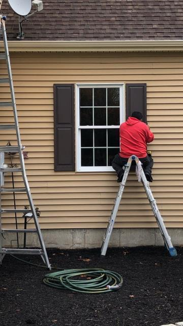 Stonington, CT - Our vinyl siding crew is installing new vinyl shutters as part the finishing touch on this vinyl siding project in Pawcatuck CT.New seamless gutters.