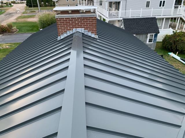 Westerly, RI - This new metal roof in Westerly RI is just about complete! Replaced the old storm damaged roof with a Drexel standing seam metal roof. Lifetime warranty