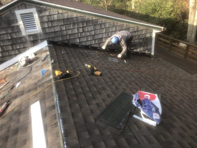South Kingstown, RI - Installing new step flashing as part of a Golden Pledge warranty. This roof will be backed BY GAF for 50 years. New PVC installed to cover the new step flashing.