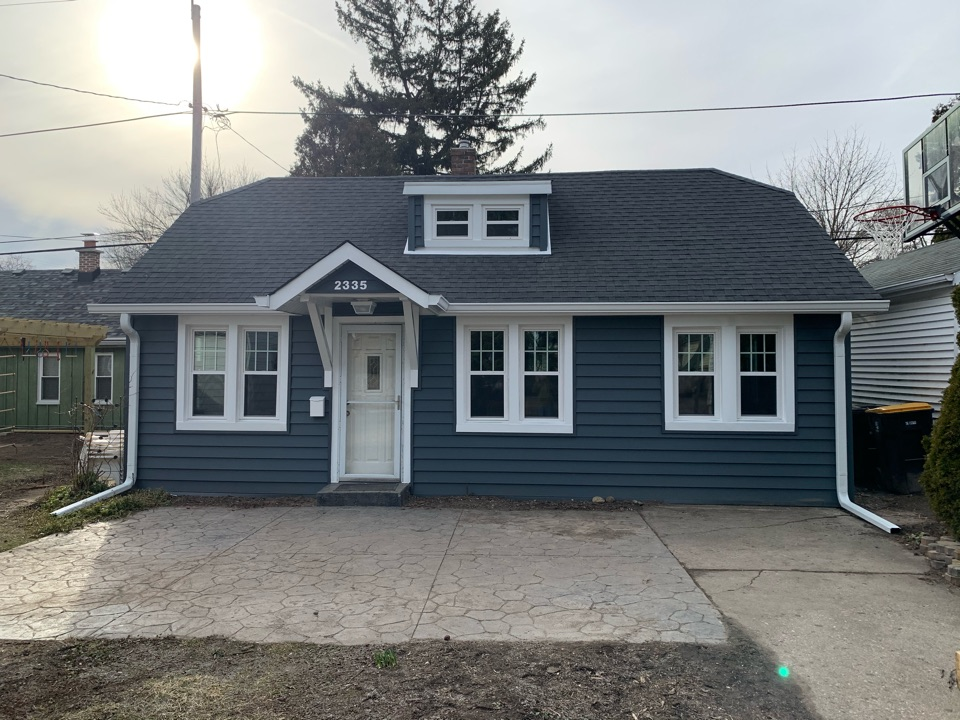 Wauwatosa, WI - Beautiful new Tosa home with all new triple pane windows and insulated Vinyl siding in beautiful Midnight Blue! The new colors and windows with grids give this home a warm cottage feel!