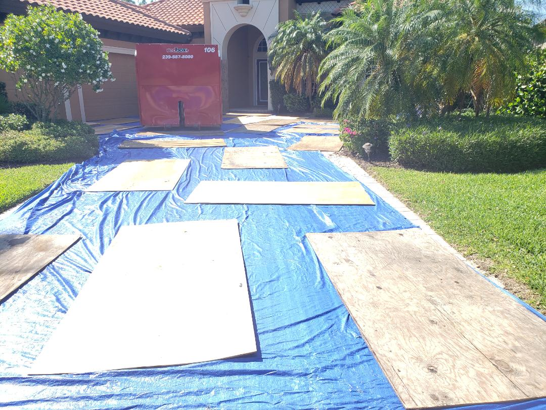 Estero, FL - Preparing a house for tile roof removal in Estero at Grandezza. Driveway, air conditioner, pool equipment, garage doors, and screens are covered prior to the project starting to protect all from damages. Afterwards we will come back to pressure wash the driveway!