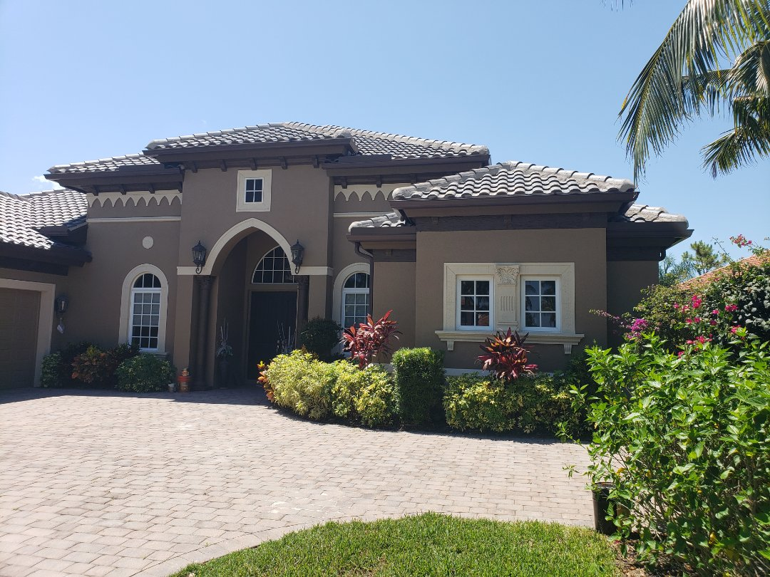 Naples, FL - After this roof was completed, we painted the new stucco and installed royal brown gutters and downspouts to match the trim and complete this magnificent project in the Majors.