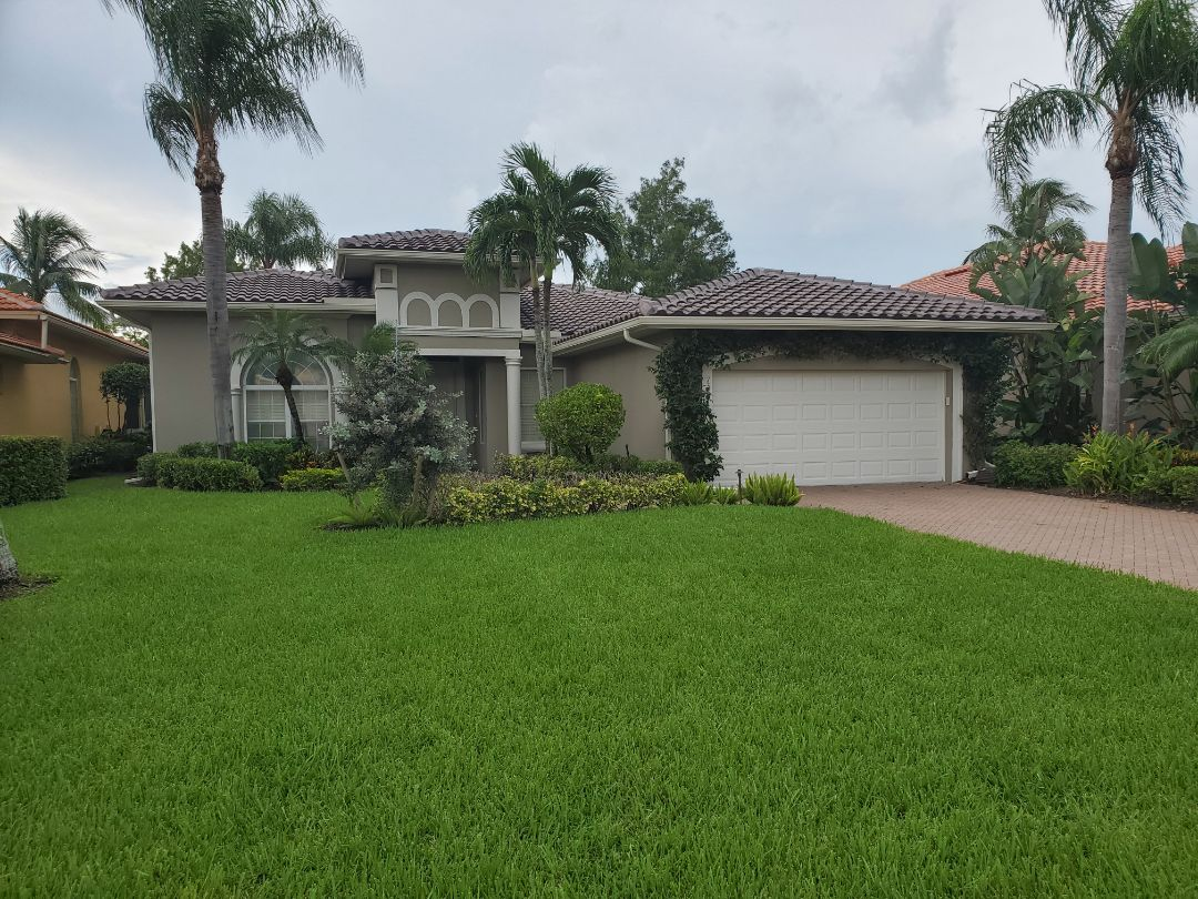 Naples, FL - After finishing this concrete tile roof, gutters were added and the house was painted. The house looks amazing!