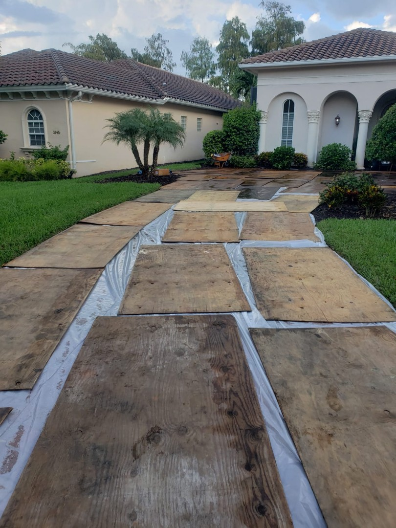 Naples, FL - Starting a new tile roof replacement in Olde Cypress. Driveway is covered with plastic and plywood to minimize any damage to paver driveway. Cant wait to see the Eagle Malibu tile be installed in November!