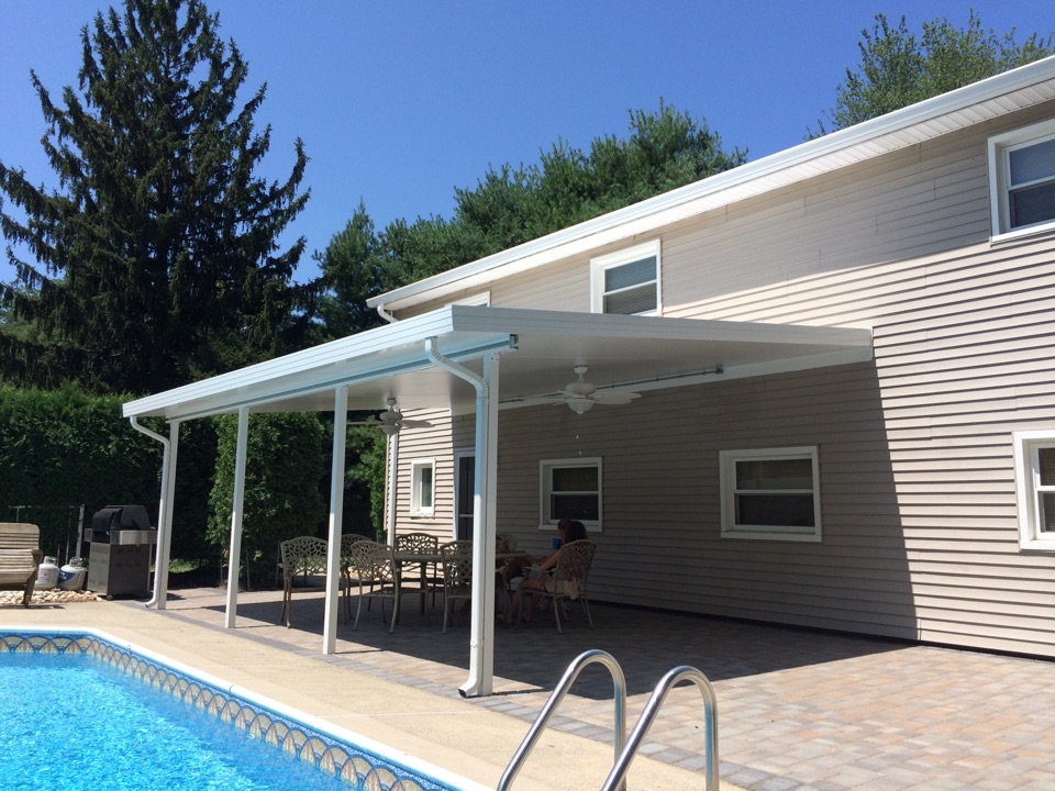 "East Brunswick, NJ - It's 100 degrees in the sun, but this 6"" Elite Aluminum Patio cover will cut the temperature 20 degrees.  Plus, the two ceiling fans installed with concealed wiring and supports (internal fan beam) will circulate air to make exterior enjoyment that much more.  This roof is approx 24'x16'.  The beautiful roof accents the pool and patio."