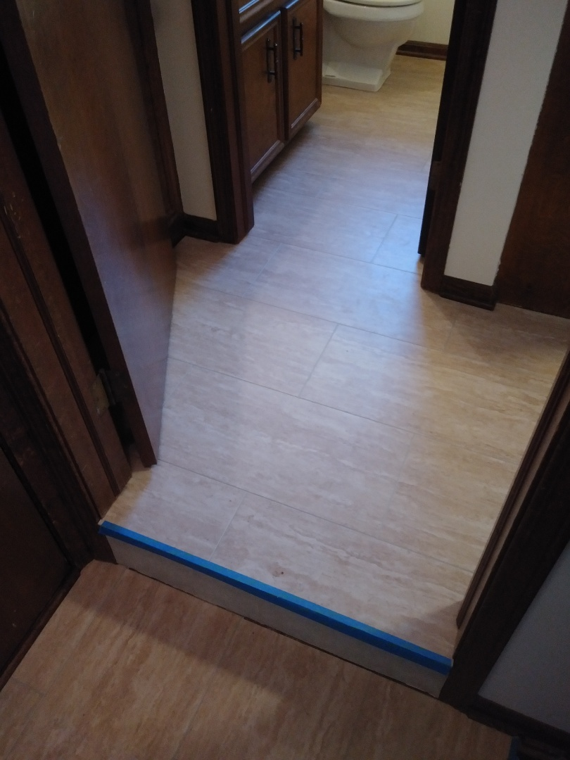 Wyoming, MI - Finished laminate floor today. I provided a different view. I removed the toilet then reset it after I finished installing the floor.  I also reinstslled the shoe and toe moldings throughout.  The blue tape is present because I am waiting on stair nosing. As soon as it comes in I will be back to install that as well.