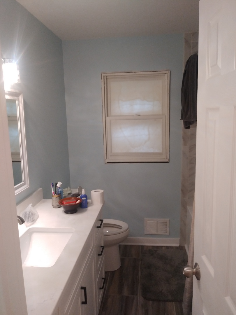 Grand Rapids, MI - Finished bathroom ( except for new window. It's on order) new drywall, paint, vanity, counter, light fixture, tub, valve, tile surround and new tile floor.