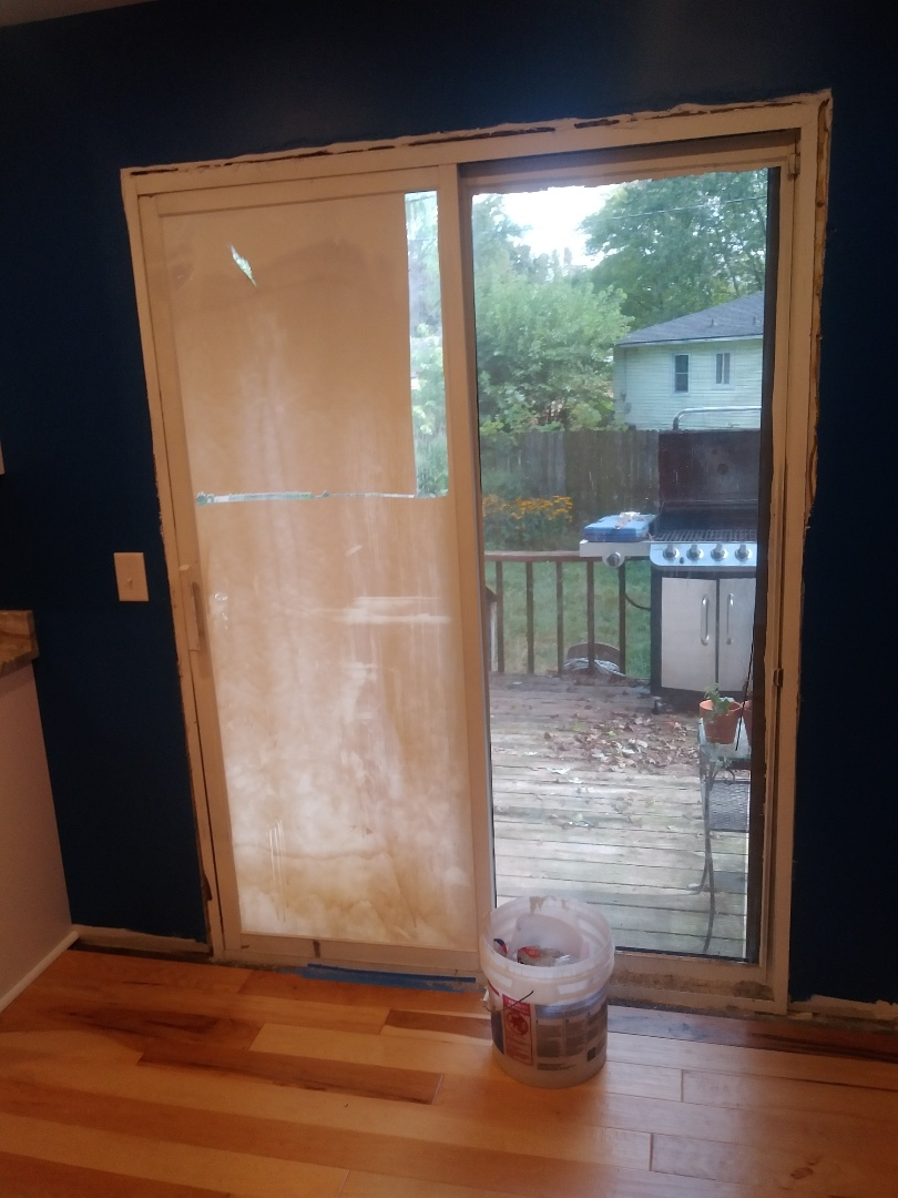 Walker, MI - The new doors and window are delayed so I'm scraping off the seal coating off the glass so the homeowners don't feel like they are living in an underground bunker