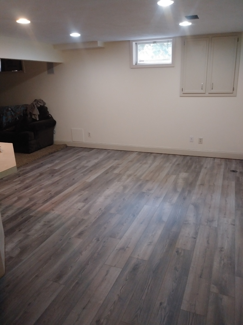 Hudsonville, MI - Finished the vinyl plank floor in the basement living room. Even spray painted the white drain clean-out on the floor to match the planks.
