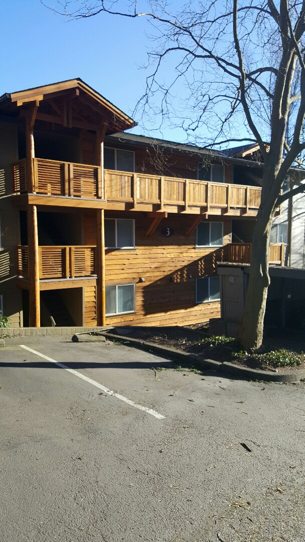 Lake Oswego, OR - Residing t1-11 buildings with stained cedar skirl siding and James Hardie lap siding. Also custom built stained peeled log entry structures. Custom built stained cedar railings with Dec tec decking.
