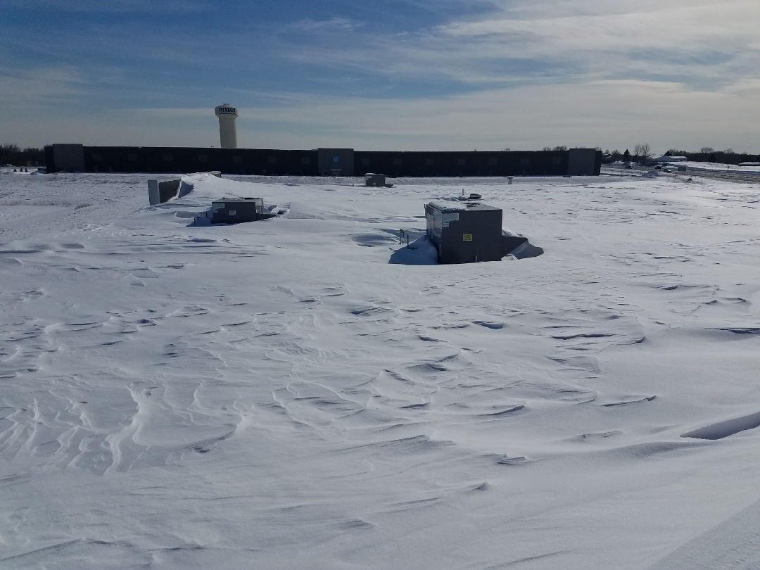 Monticello, MN - Removed snow build up around roof top units on commercial building in Otsego