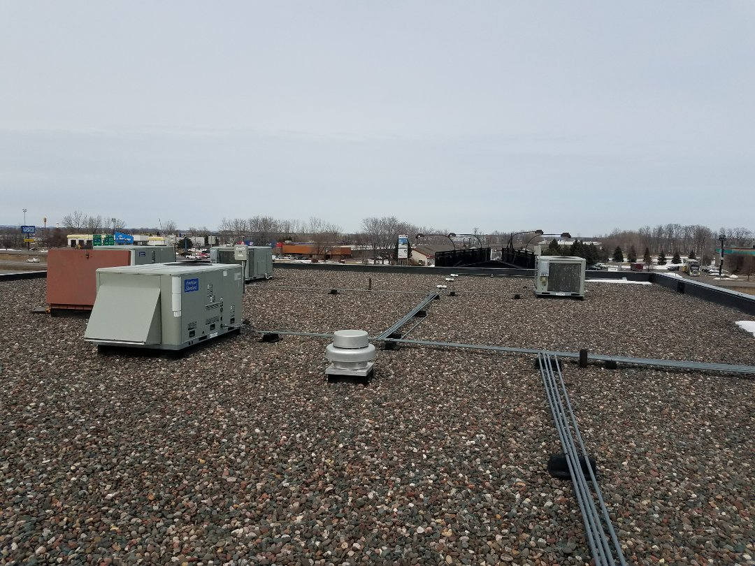 Elk River, MN - Commercial rooftop maintenance and air conditioner cleaning on 8 American standard units in Rogers