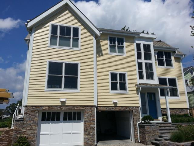 Westport, CT - This new construction home in Westport, CT needed a low-maintenance exterior that would last for decades. The general contractor knew that James Hardie fiber cement composite siding was the perfect product. After meeting with both the GC and the homeowner, the Burr team installed Hardie's Artisan siding in Woodland Cream. The Artisan profile is thicker than the traditional clapboard, creating thicker shadow lines and a rich aesthetic.