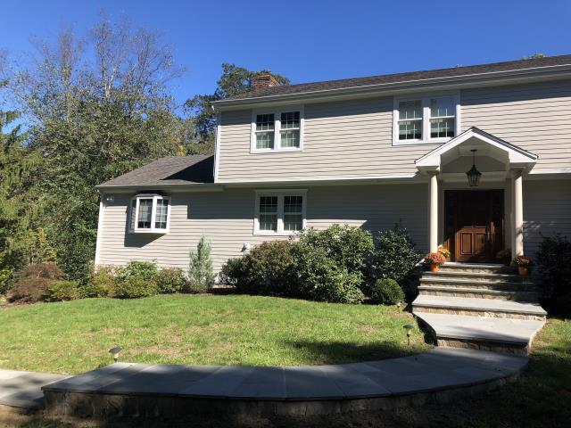 Stamford, CT - This Stamford home was remodeled using James Hardie clapboard in Cobble Stone with a cedarmill finish to mimic the appearance of traditional wood siding. Unlike wood siding, James Hardie is low maintenance, pest resistant, AND holds a 30-year warranty. Our favorite part of this project was the custom portico build in the front entryway. With overhead lighting and a tall gable, this portico welcomes friends and family inside.