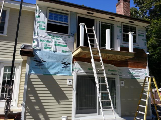 Stratford, CT - In progress remodel in Stratford, CT! This homeowner picked James Hardie fiber cement siding in Sandstone Beige. Our carpentry team is working on building out a second story overhang to give the couple outdoor access from the master bedroom.