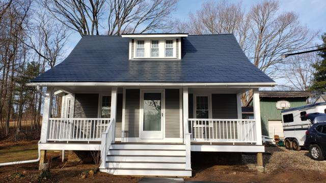 Guilford, CT - Final product in Guilford! The Burr team replaced the existing cedar siding with James Hardie fiber cement clapboard in Aged Pewter. Our carpentry crew completely remodeled the front porch with TimberTech Azek composite decking in Dark Hickory. Now, these homeowners can enjoy the outdoors, rain or shine.