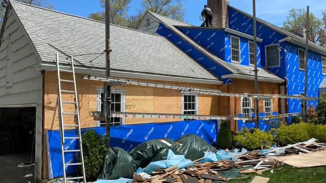 Greenwich, CT - Day one of tear off and wrap in Darien, CT. The crew is inspecting the sheathing and checking for rot before installing Henry Blueskin VP100 house wrap to protect the home until its time for James Hardie fiber cement siding.
