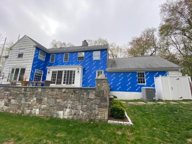 Greenwich, CT - The crew is making great progress in Darien, CT. The old cedar siding is coming down and Henry Blueskin self-adhesive house wrap is being used to protect the sheathing from exterior elements until siding installation begins.