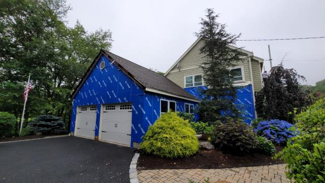 Shelton, CT - In-progress shot of a home in Shelton with Henry Blue Skin VP100 house wrap being installed and the old siding removed. The homeowners will be adding James Hardie Fiber Cement siding to give their house a fresh exterior.