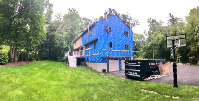 Ridgefield, CT - Out with the old and in with the new, this Ridgefield home is getting a full exterior makeover including new Marvin Elevate windows, Marvin French doors, and James Hardie Fiber Cement siding. This in-progress shot shows the old siding removed and the Henry Blueskin VP100 house wrap added. Next up, window installation!