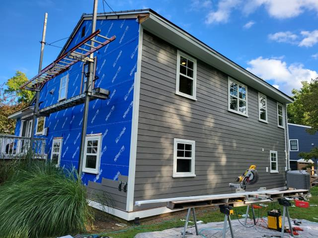 Stamford, CT - In-progress photo here in Stamford as our team works to install new James Hardie fiber cement Lap Cedarmill siding in Aged Pewter with AZEK PVC trim in white. It is so exciting to watch the house transform before your eyes.