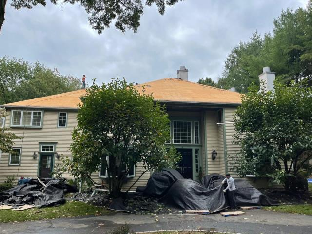 Westport, CT - Here in Westport, we are removing the old shingles from this roof and installing new CertainTeed LandmarkPro shingles in Weathered Wood. The renovation also includes new gutters and Velux solar venting skylights.