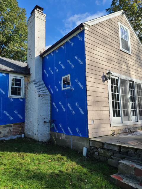 Stamford, CT - This home will be made new by installing James Hardie Arctic White smooth fiber cement siding, and new Marvin Elevate windows throughout the home. The first step is to remove the old siding and to prep the home with Henry BlueSkin VP100 house wrap before adding the new windows and siding.