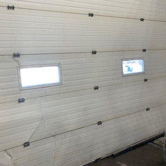 Service Call: Overhead Door  Issue: Overhead Door stuck open  Work Performed:  Put the cables back on the drums Replaced two #5 Hinges  Cycled door to ensure safe and proper operation of door.
