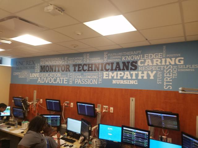 Raleigh, NC - When UNC Rex Hospital needed graphics to celebrate their patient monitoring staff they called Capital Wraps.  Check out the wood paneling and word cloud above.  Sitting in a closet sized room matching 5-15 patients all day is a difficult yet extremely important job.  We are happy to help create a awesome environment for them with these wall mural graphics.