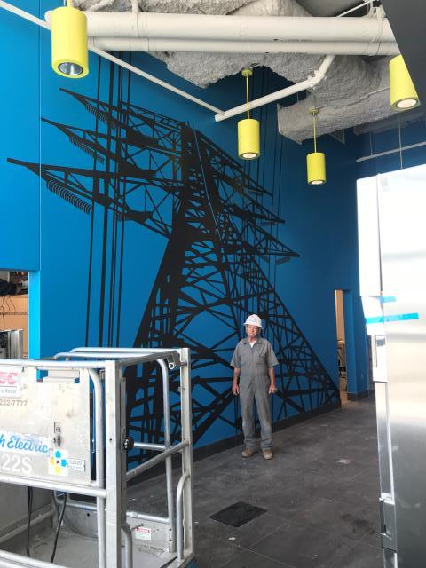 Raleigh, NC - When the Electric Company Calls you up and asks for some LARGE graphics in their conference room, you strive to provide them with 16' and 23' wide graphics that highlight what they do.  This wall graphics is a mural but it is also done as cut graphics - 5 18' high panels were aligned perfectly to produce this power line silhouette for their conference room.  The 6' installer shows relative size for the mural and the lift in the front was required to install it.