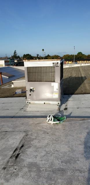 Installing a heating and air conditioning package unit on a commercial building in Salinas.