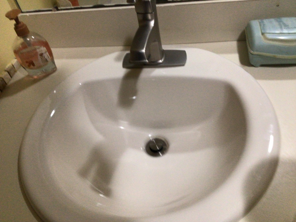 Clean debris out of drain to prevent sink from smelling in Brick