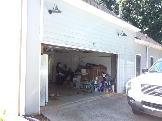 Cumming, GA - Servicing garage door. Lubricating, adjusting springs, and adjusting motor. Replacing garage door sensors.