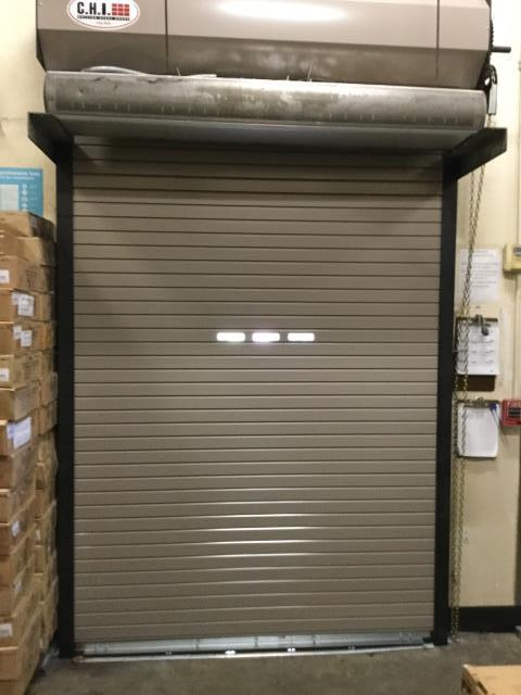 Installing 6'x9' insulated, rolling steel doors with vision lights.