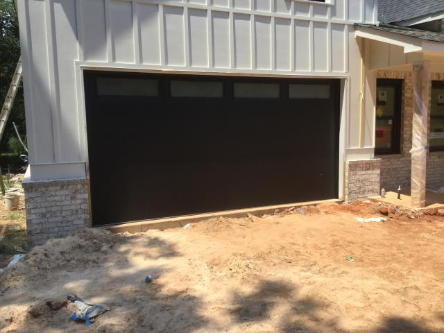 Installing CHI Flush Panel 16' x 8' garage door with frosted windows, raised panels. Installing LiftMaster 8355W garage door opener. Serving garage door.