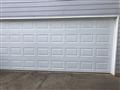 Installing two 8'x7' solid white garage doors. Installing torsion springs and tracks. Installing two LiftMaster garage door openers.