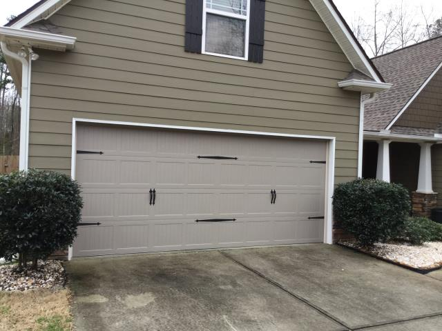 Lawrenceville, GA - Installing 16x7 carriage style garage doors in sandstone with decorative hardware.