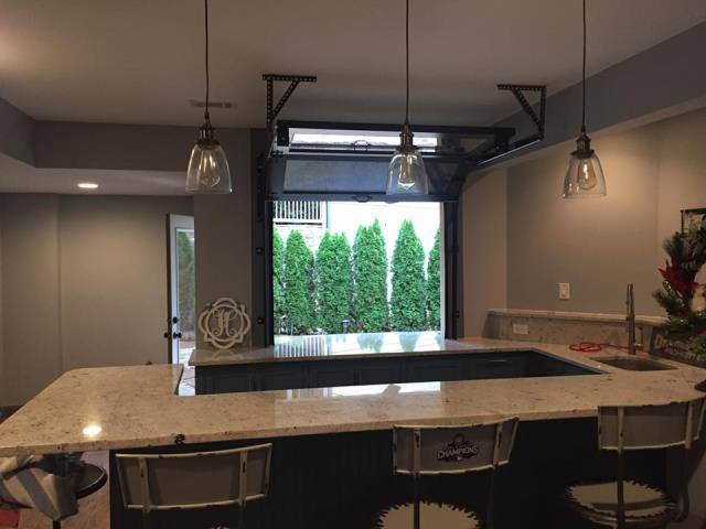 Cumming, GA - Installing a 5x4 full view glass & aluminum garage door that is powder coated black. Door sits on a counter top to connect the indoor kitchen to the outdoor living space.