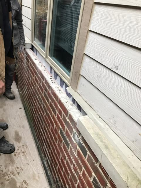 Highland Park, IL - Residential masonry project involving tuckpointing & replacement of stone ledge.