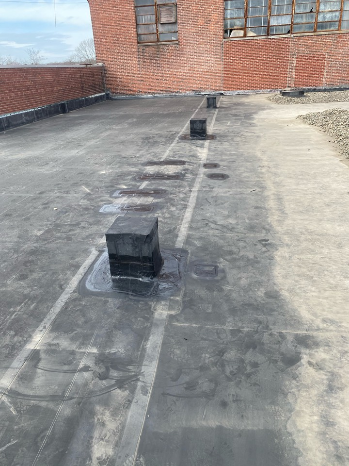 """Braintree, MA - Found multiple holes in leak area, as well as multiple patches taking water on a EPDM ballast roofing system. Cleaned areas and patched with Carlisle 12"""" elastoform and lap sealed"""