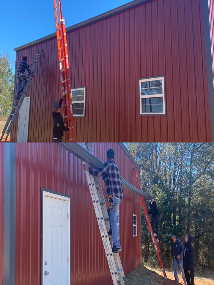 Baker, FL - Installing a 6 inch seamless gutter on this  metal pole barn in Baker Florida This color is called tuxedo gray we are using a 6 inch k  style Gutter
