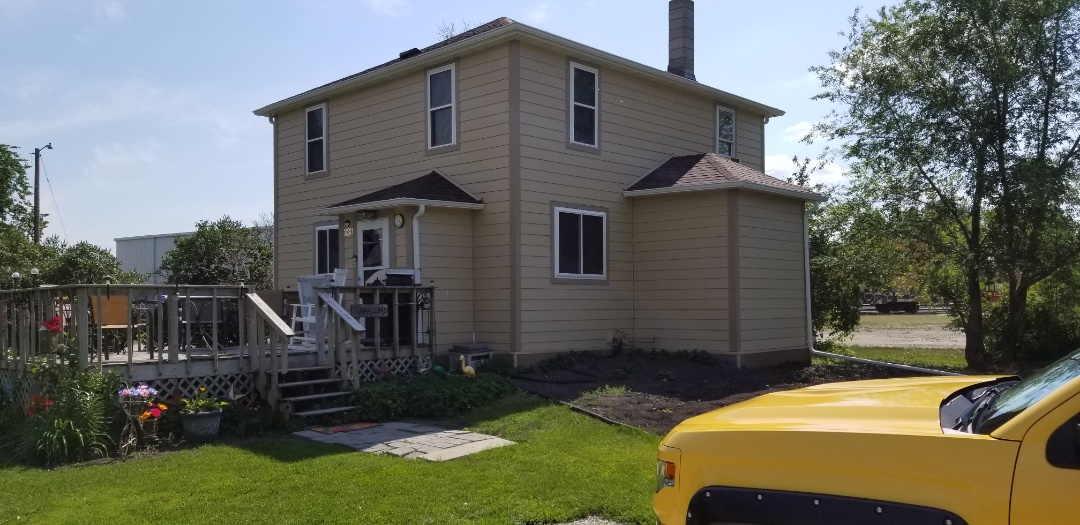 Grandin, ND - Homeowner is enjoying the new Owens Corning Duration brownwood shingles, white seamkess gutters and James Hardie Autumn Tan siding