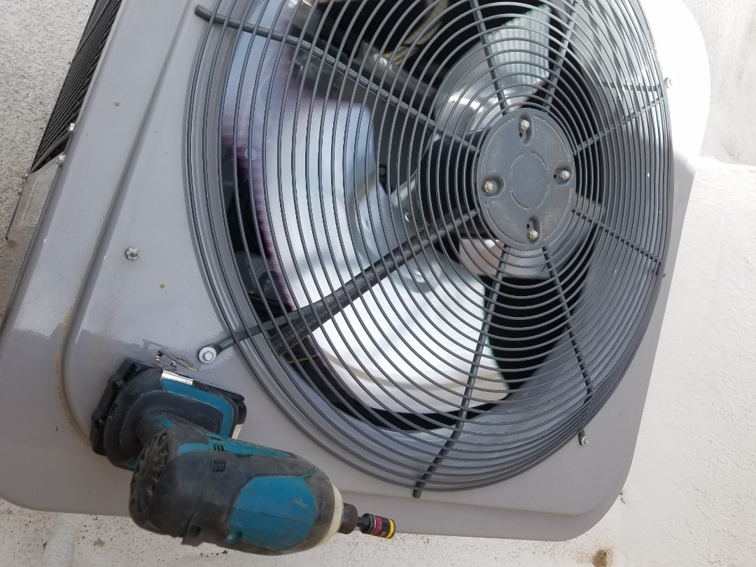 Doing a repair on an air conditioner unit.