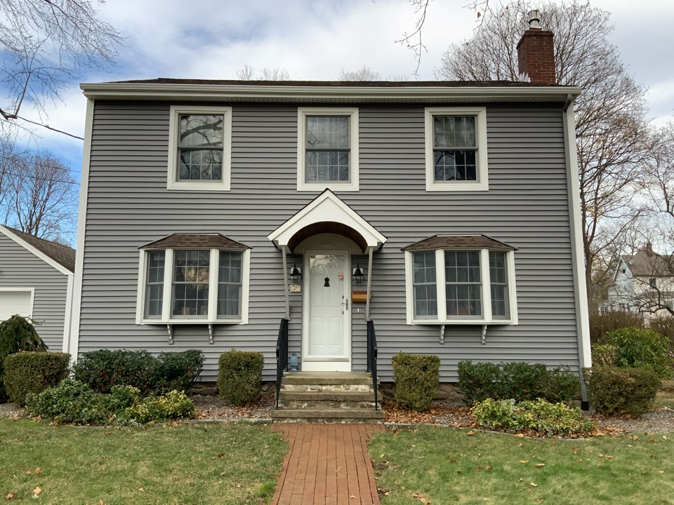 Watertown, CT - Installed new insulated Certainteed monogram siding in Charcoal Gray with Colonial white window and door trim and fluted corner posts. New seamless gutters with Leaf Blaster Pro gutter protection