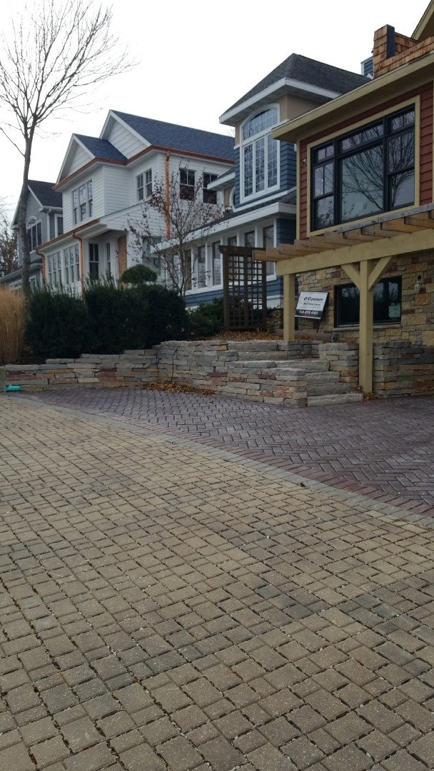 Delavan, WI - Stopped by to inspect a snapstone retraining wall with a permeable driveway t hat we just completed.  The retaining wall is Chilton snap stone while the driveway is Unilock Town Hall.  The homeowner was concerned about rain run off into Delavan Lake so we recommended we do a permeable paver driveway to eliminate anyband all rain water run off.  Phase 2 of the project is custom handrails as well as low voltage landscape lighting.