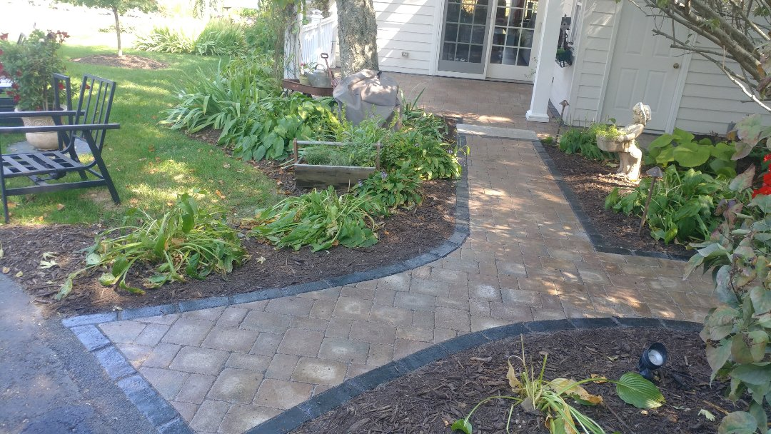 Burlington, WI - Stop by to inspect a project we finished last fall. The homeowner had the deck and old asphalt removed and we installed a brand Unilock Brussels paver patio and sidewalk with Unilock Town Hall accent pieces