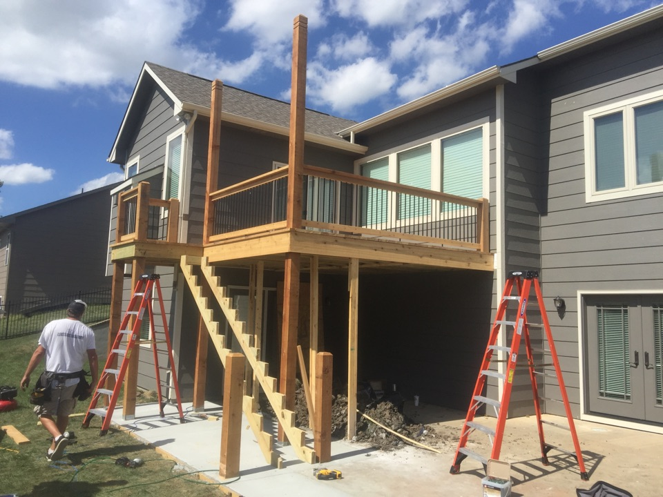 Wichita, KS - New wood deck with metal balusters and concrete pad. Extending posts for shade cover.