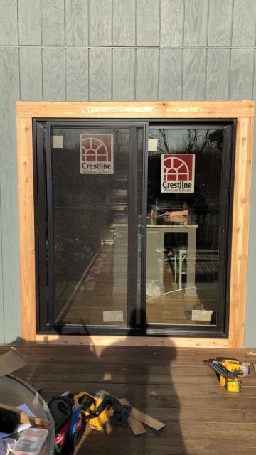 Overland Park, KS - Installation of new black exterior framed Crestline patio sliding door with prefinished interior stained trim.