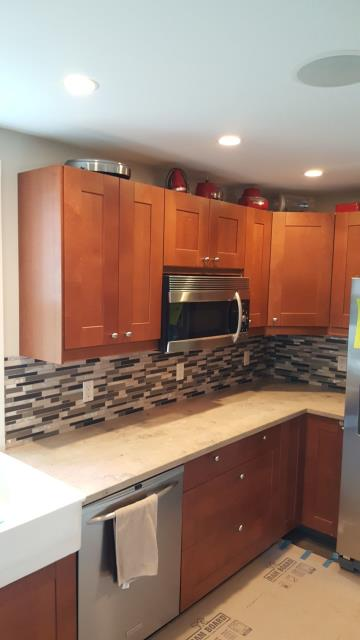 Kansas City, MO - Installation of modern, stylish backsplash to update the kitchen to a more contemporary look. The backsplash helps the cabinets and counters pop out  & stand alone while also remaining cohesive.