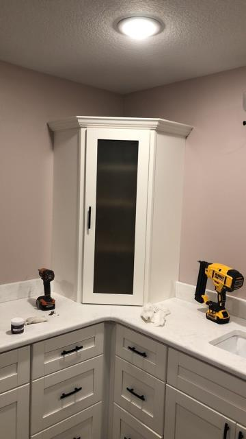 Raymore, MO - Master Bath corner cabinet with glass door insert.  Beautiful addition to any bathroom.